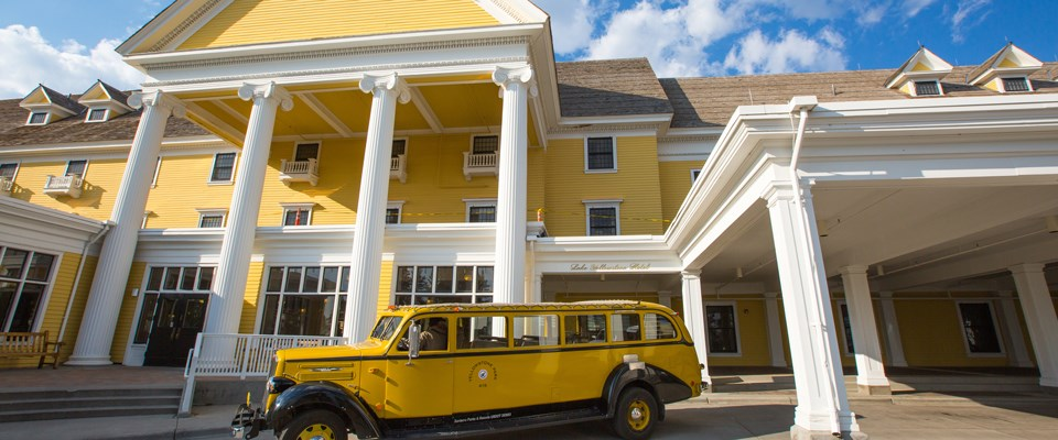 A historic yellow vehicle in front of a historic yellow building