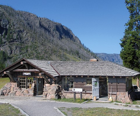 A one-story stone and log building with wooden shingles beneath a mountain