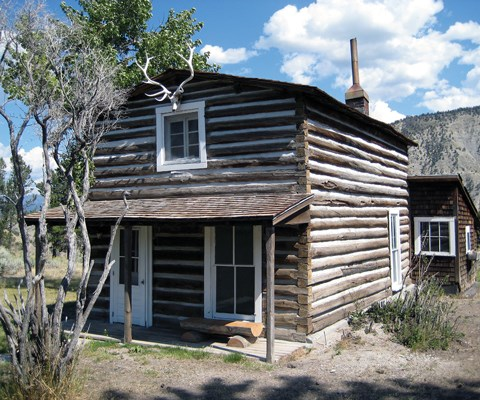 A two-story log cabin with porch and elk skull below the roof peak