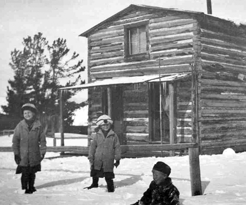 Three children in winter clothes stand in front of a two-story log cabin