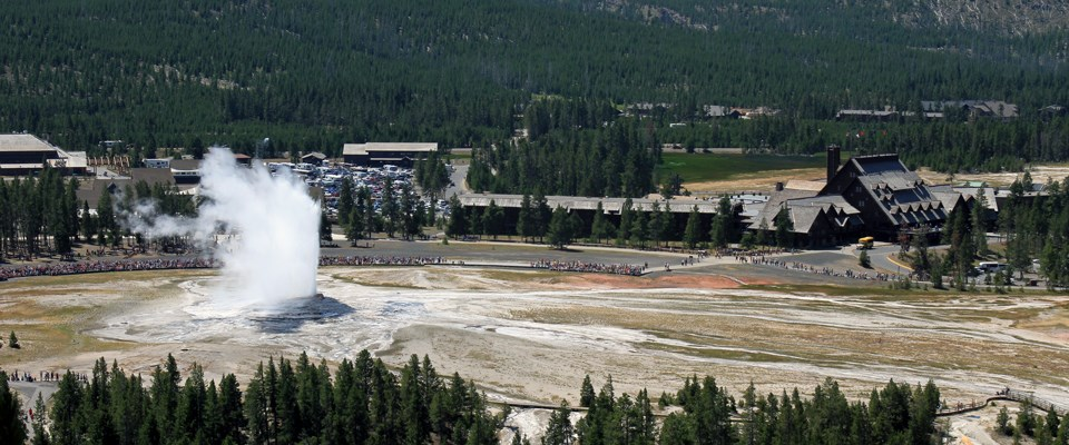 An aerial view of bleachers for viewing Old Faithful, the geyser erupting, the inn and lodge, and other buildings