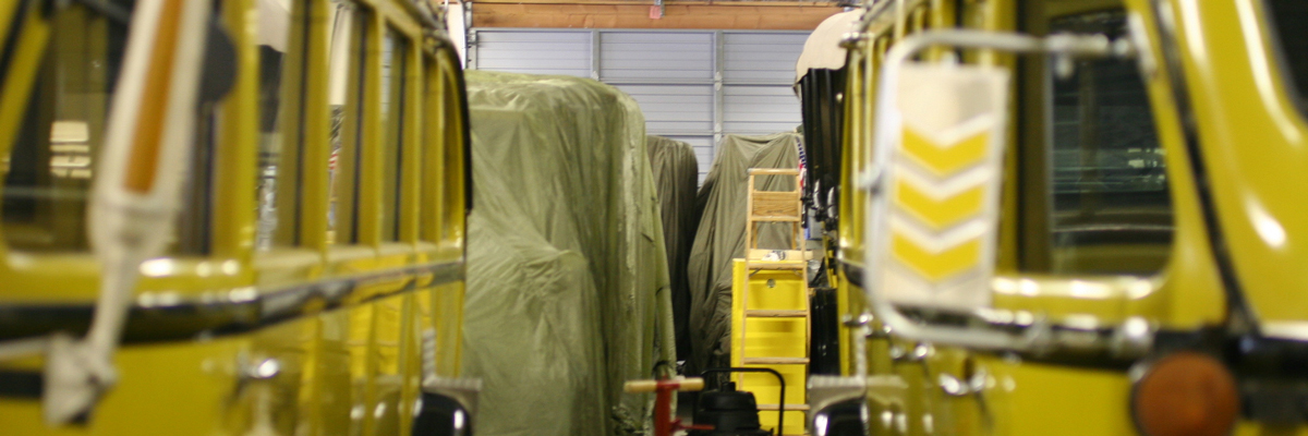 Yellow historic vehicles at the front of a line of vehicles covered in drapes in a garage