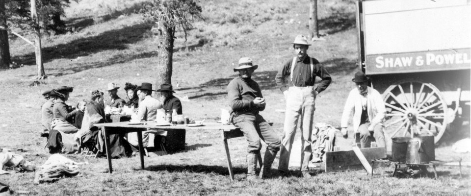 A black and white photo of people sitting at a table eating and three men resting next to a wagon