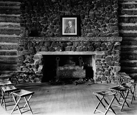 A portrait of President T. Roosevelt sits on the mantle of a stone fireplace with stools arranged in front of it