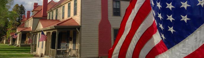 An American flag flutters in front of historic yellow and red buildings
