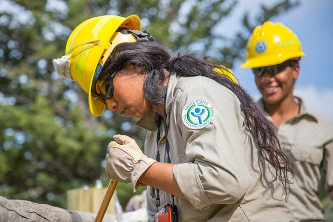 Native American youth digging, wearing a yellow hard hat. shoulder patch displays the Yellowstone Conservation Corps logo.