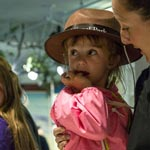A young girl in a Junior Ranger rat looks up
