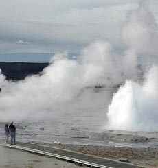 Two visitors watch from a boardwalk as Great Fountain Geyser erupts