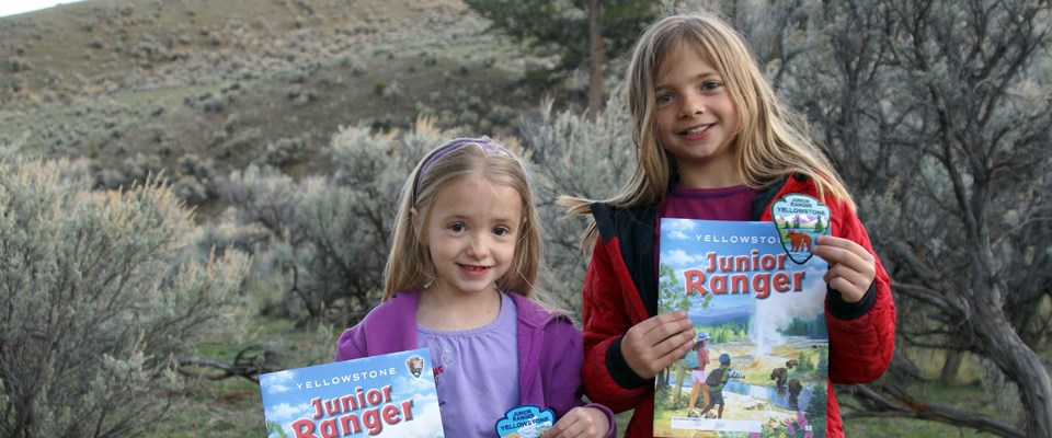 Two young junior rangers hold up their books and patches