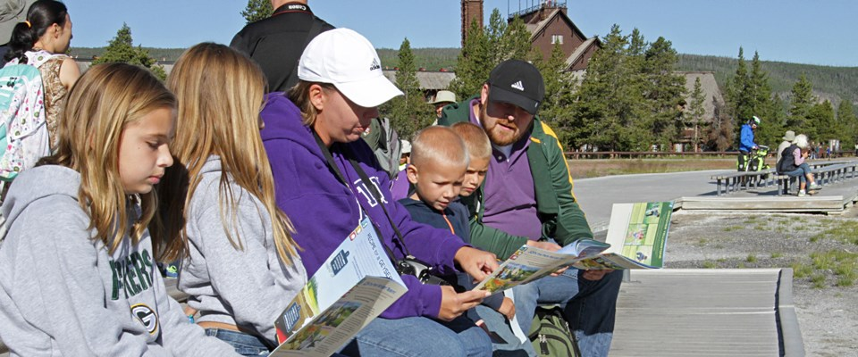 A family sits on a bench in front of the Old Faithful Inn working on Junior Ranger books