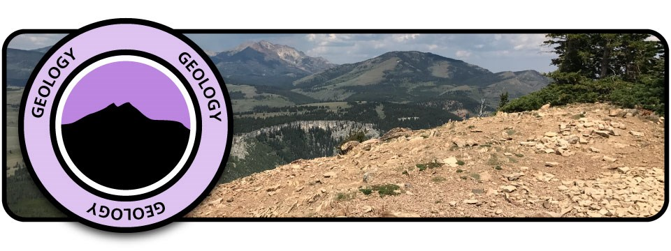 "Purple badge with silhouette mountain and word ""Geology"" over image of a rock mountaintop overlooking other mountains."