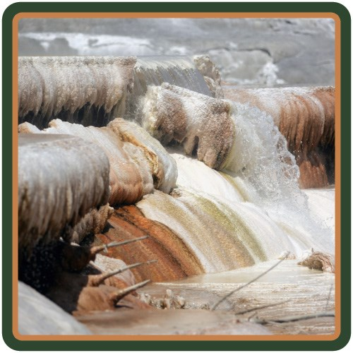 Close-up view of water flowing down white, yellow, and orange-colored travertine terraces.