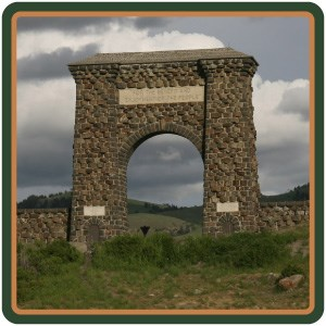 The stone Roosevelt Arch standing above a hillside of grasses and shrubs.