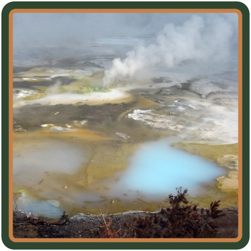 Steam rises from a hot spring that ranges from blue and yellow to milky white.