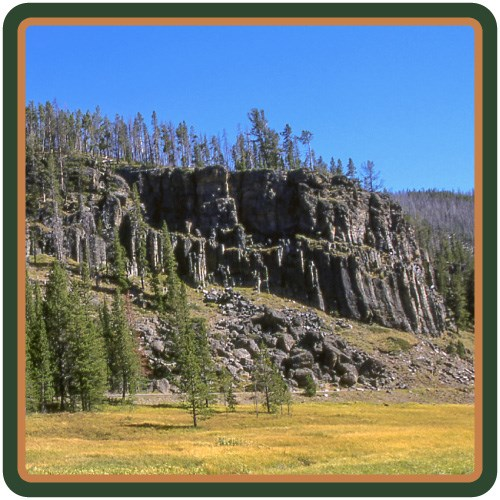 A jagged, gray cliff rises above a wetland and meadow.