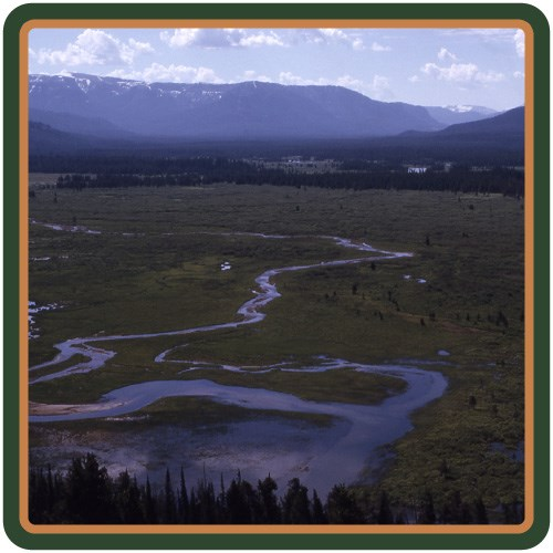 The Yellowstone River meanders through a wide-open valley with mountains in the background.