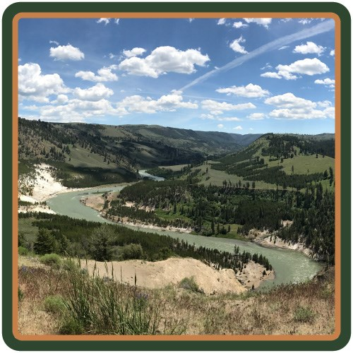 Yellowstone River, a greenish-blue, winds through a valley.