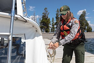 A park ranger unties a boat from a dock