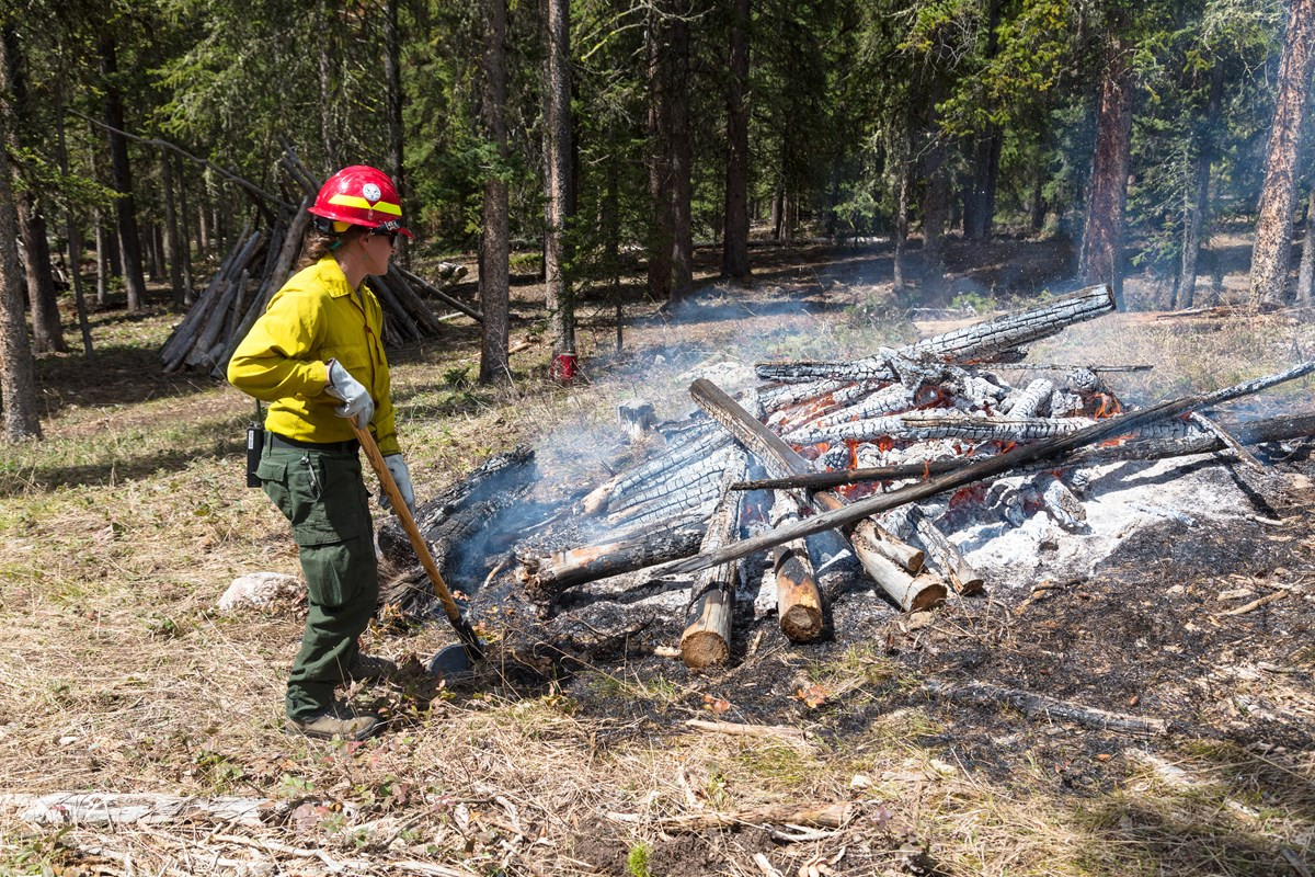A wildfire crew stands close by a large pile of burning logs.
