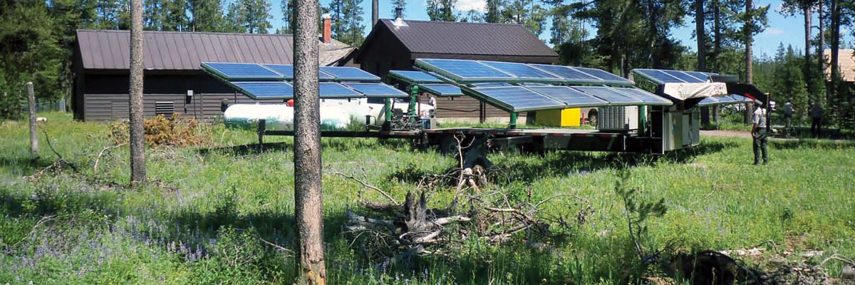Solar panels unfolded from a trailer next to a ranger station