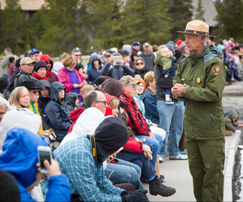 A male park ranger speaks to seated visitors on a boardwalk