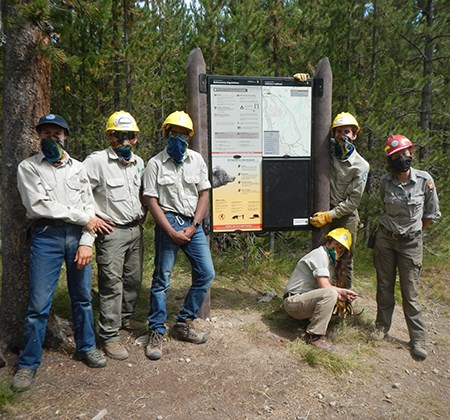 A group of young adults with hard hats stand next to a large sign on a trail.