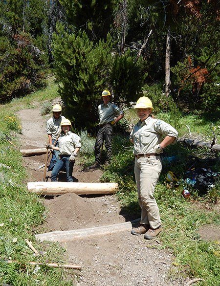 A group of young adults with hard hats stand on a trail in the wilderness