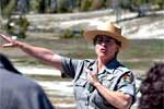 A ranger gestures while talking to visitors.