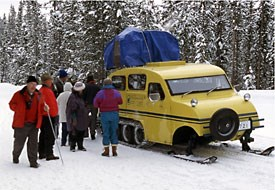 Visitors stand in the snowy landscape by a snowcoach.