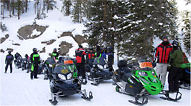 Group of winter visitors getting ready to take off on snowmobiles.