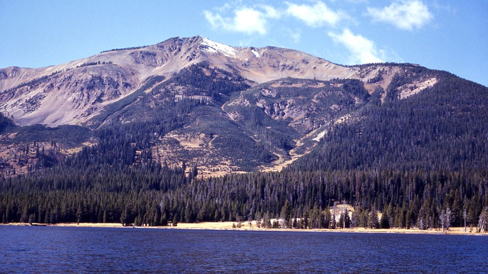 Tall mountain rises from the shore of an alpine lake.