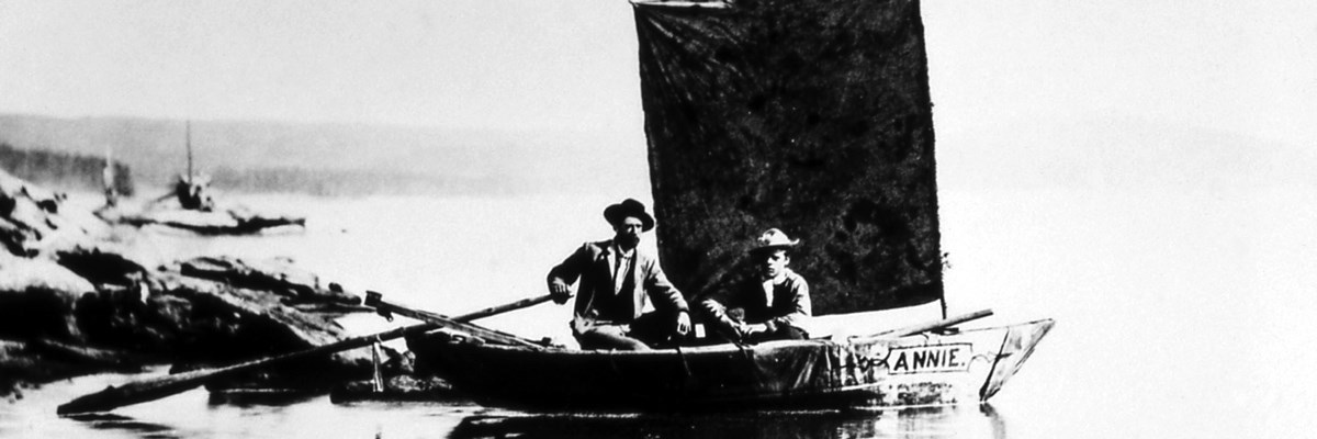 Two men sit on a wooden boat with a square sail