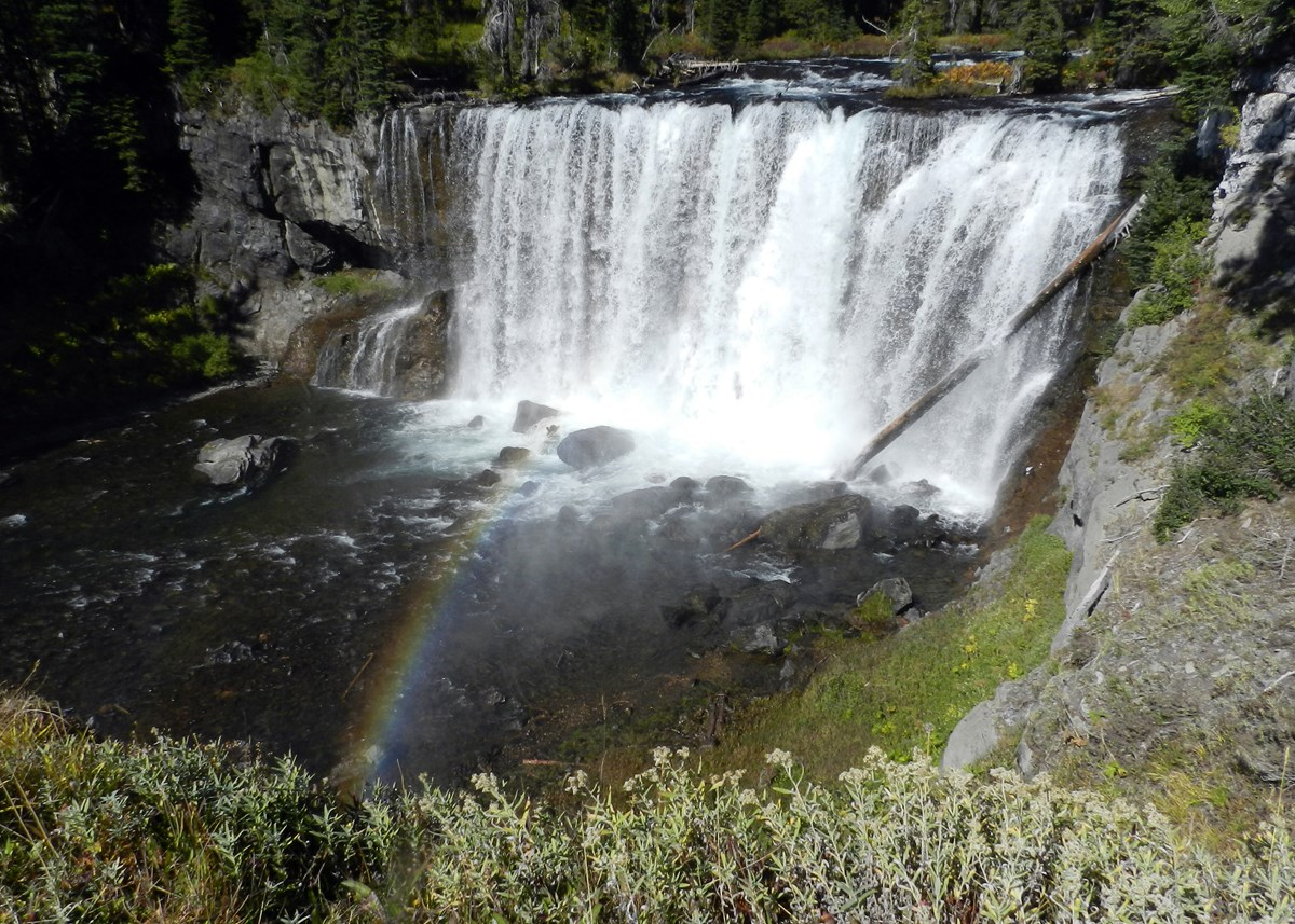 A wide waterfall drops over a gray rock cliff with a rainbow glowing in the spray.