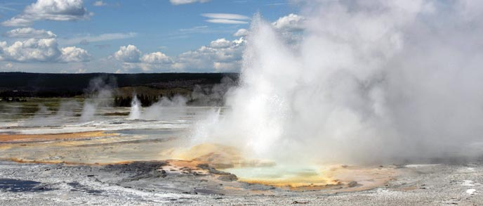 Orange, blue, and white pools surround erupting and steaming geysers