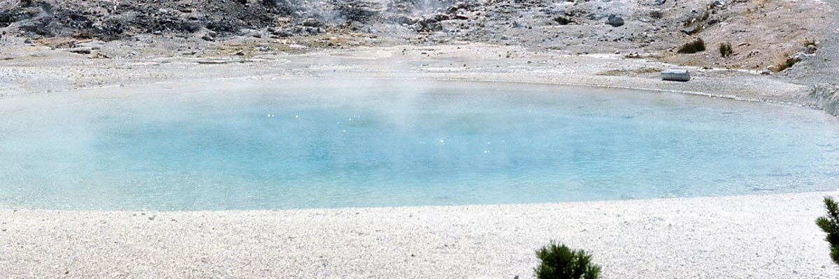 A blue steaming pool surrounded by pale rock