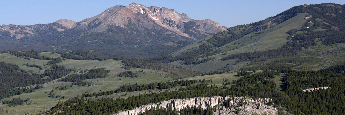 A mountain with sloped green hills and bare rock at the top of a hill in the foreground