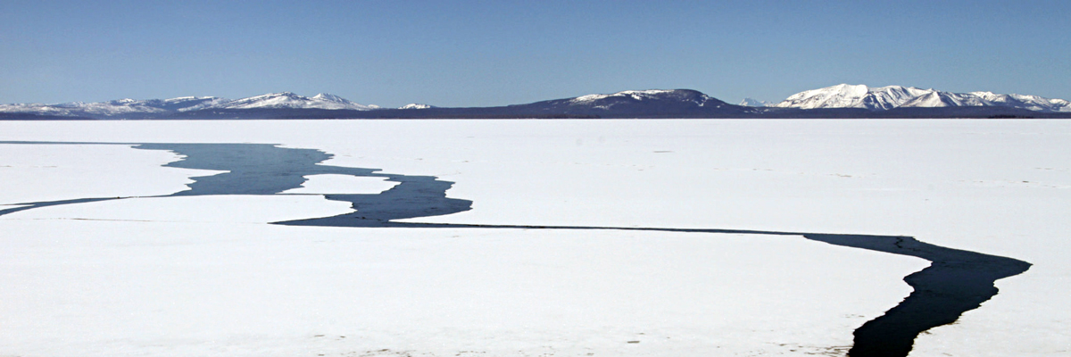 Distant snow-covered mountains and an ice-covered lake with large cracks