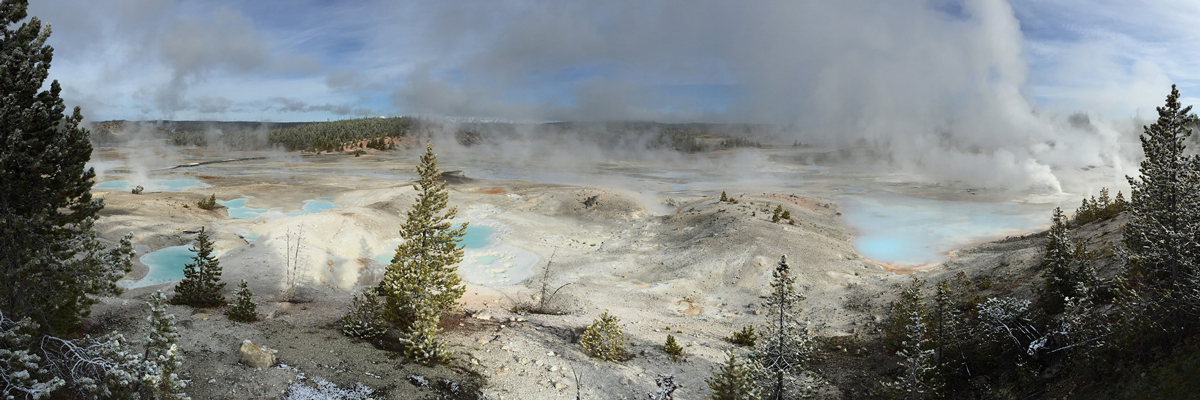 Steam rises from a wide geyser basin with light blue pools