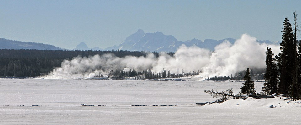 A snow-covered lake with steam rising at the edge and mountains in the background
