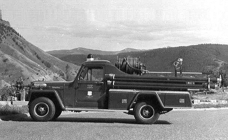 A older style of truck has a fire hose wrapped on a spindle and is parked on the pavement in front of a mountainous and forested landscape.
