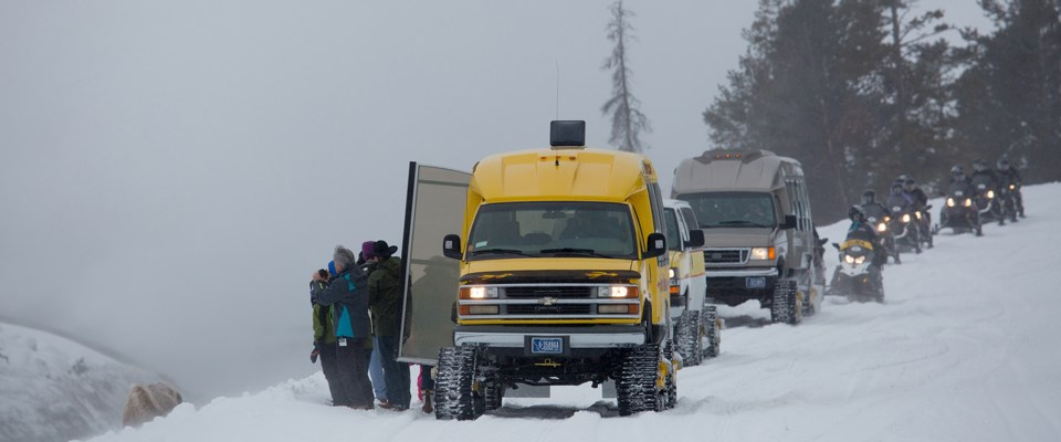 Visitors stand outside of open doors to a van on mattracks with a line of oversnow vehicles and snowmobiles along the side of a road