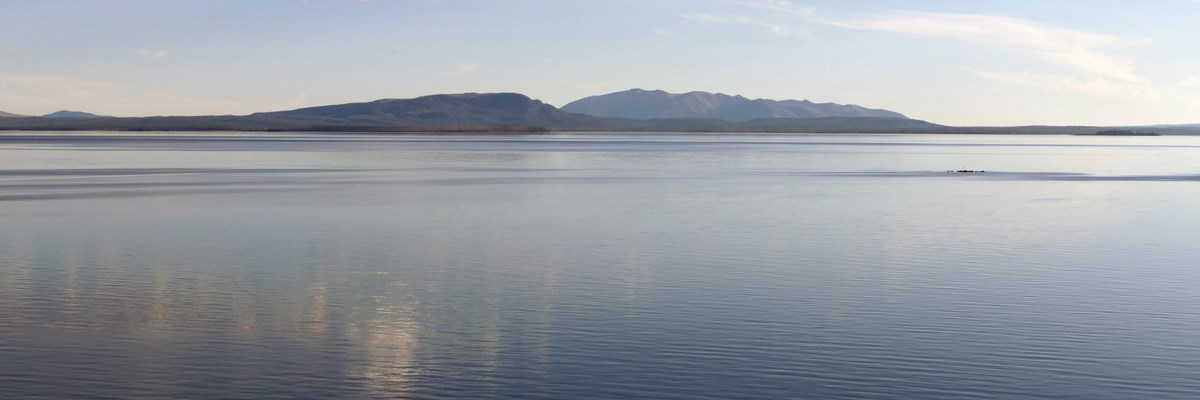 Calm waters of a large lake in front of mountains