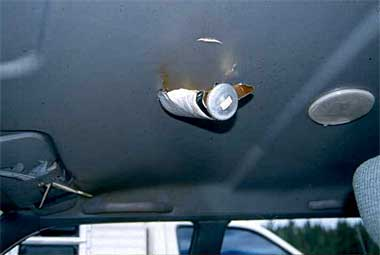 Bear spray canister embedded in ceiling of vehicle.