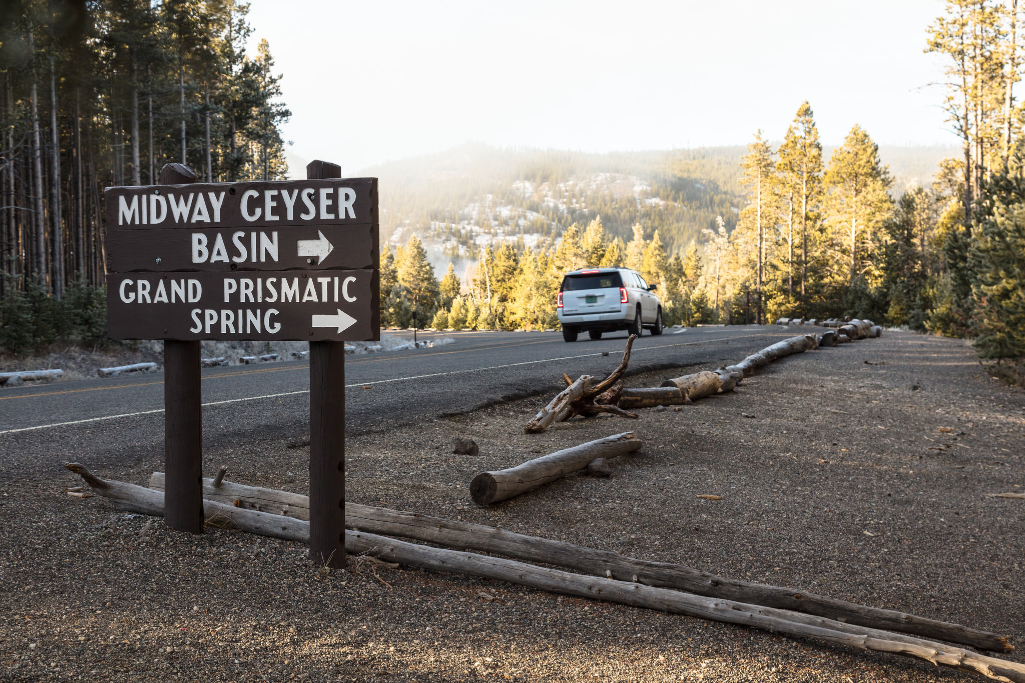 A vehicle driving by a wooden sign with the words Grand Prismatic Springs