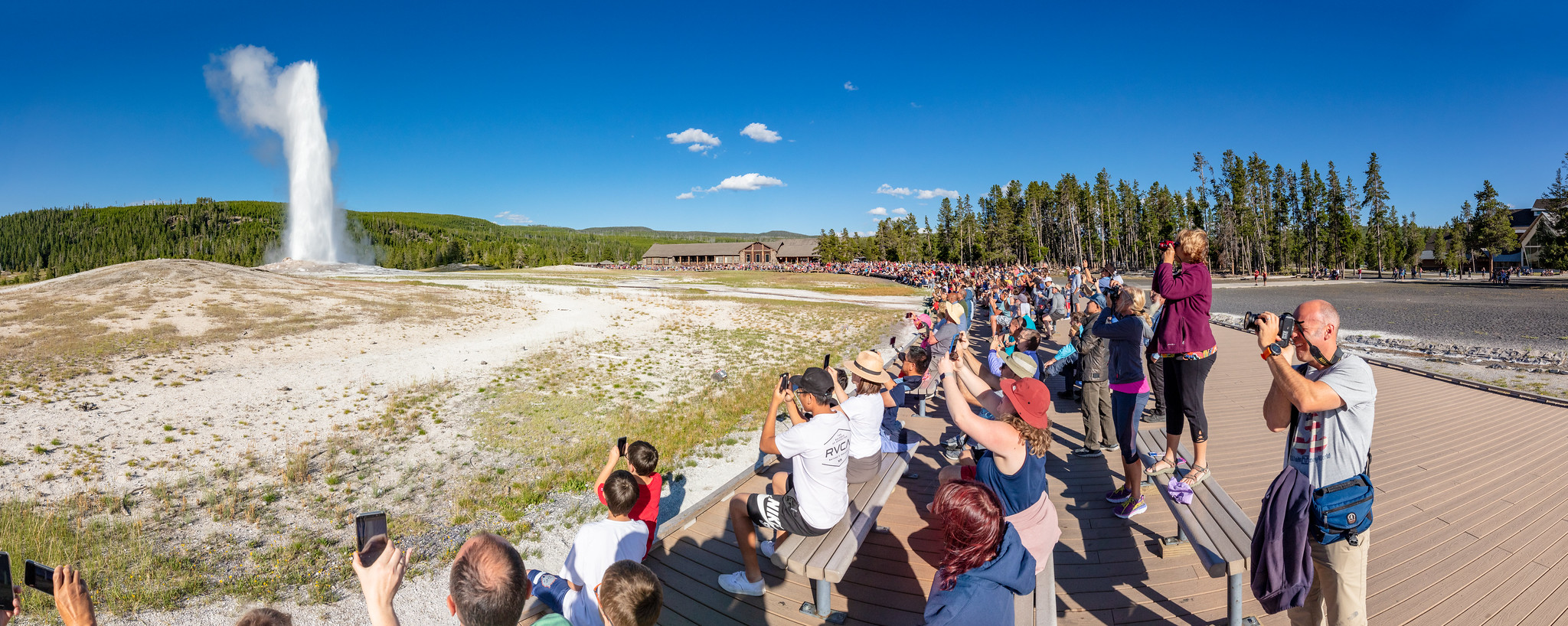 A group of people watch an Old Faithful eruption