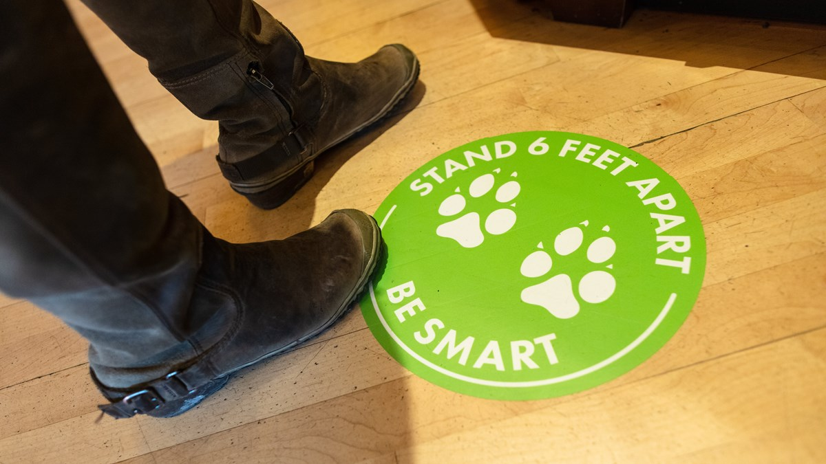 A person's feet standing near a sticker on the floor with text about social distancing