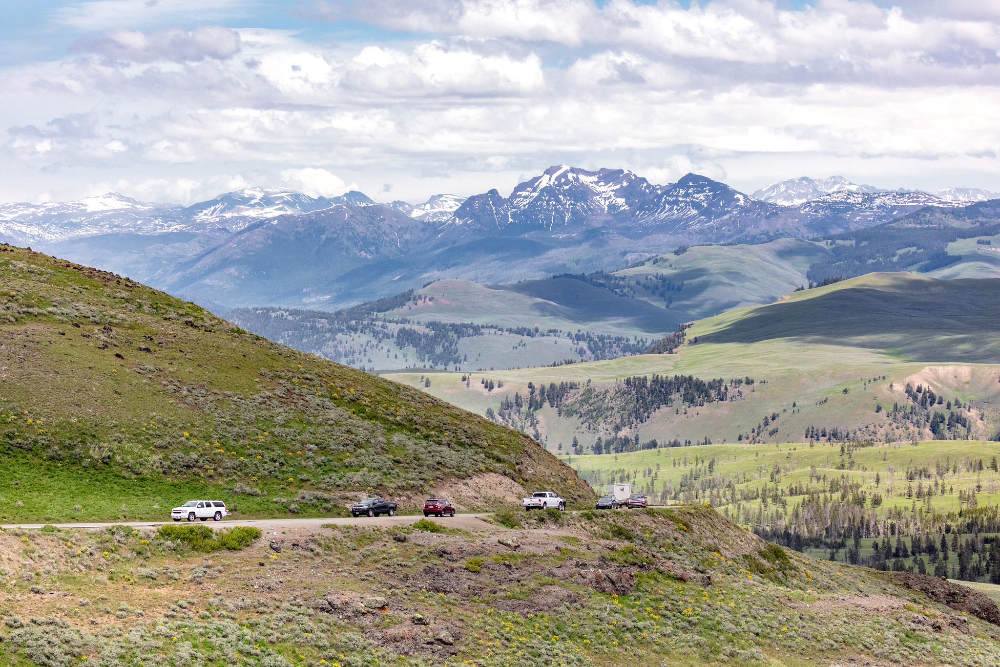 Cars driving on Dunraven Pass with mountains in background
