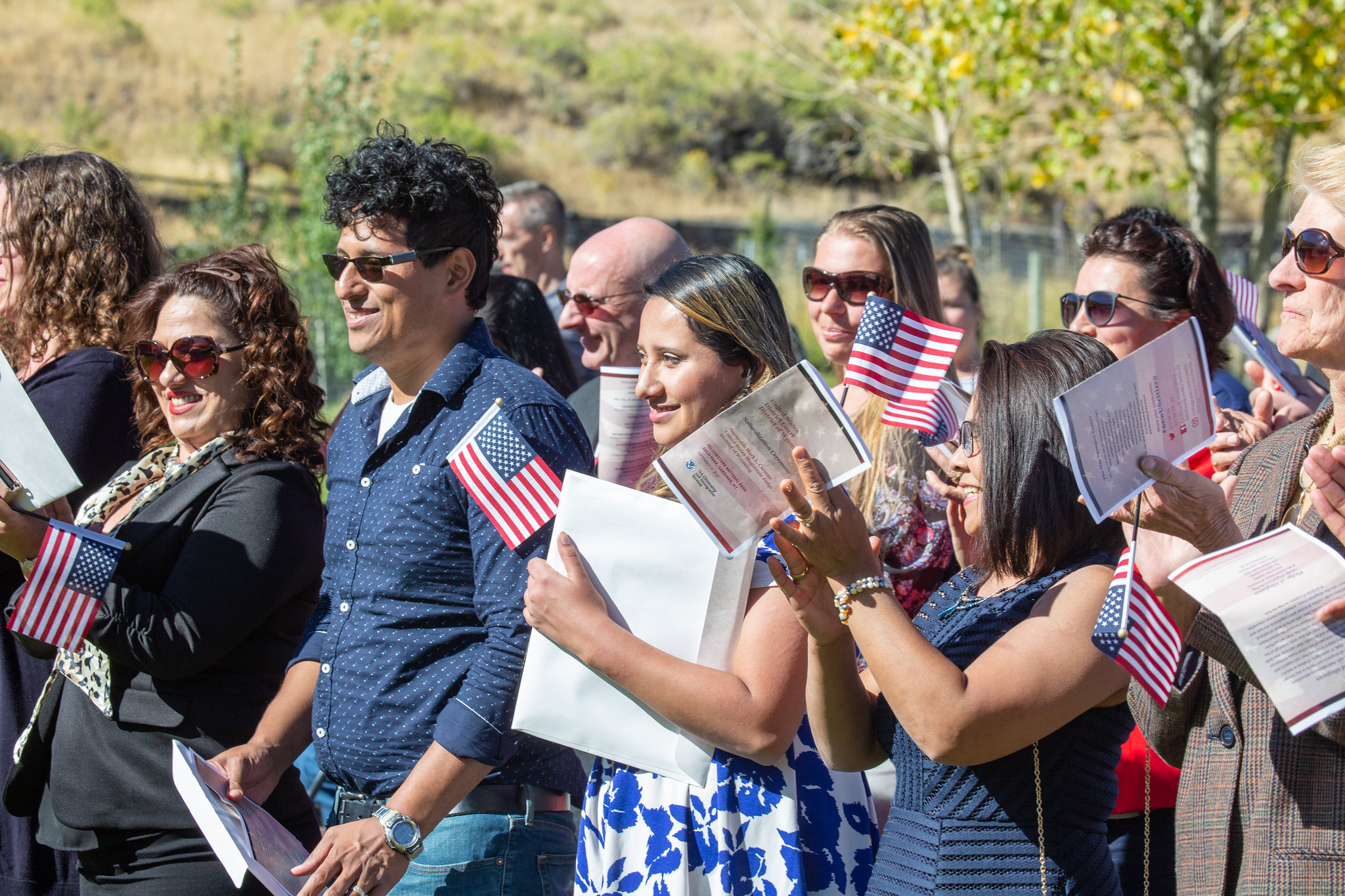 New citizens smiling and holding programs and flags