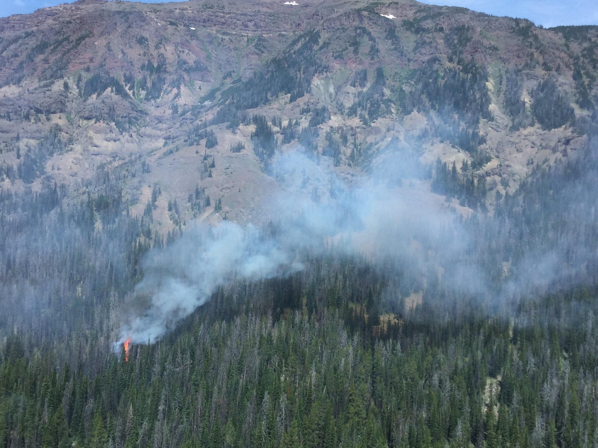 flames from a small wildfire in mountainous terrain