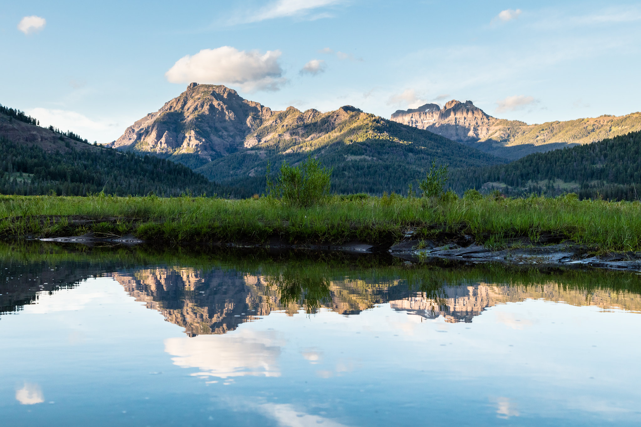 Mountains are reflected in the still waters of Soda Butte Creek at sunset